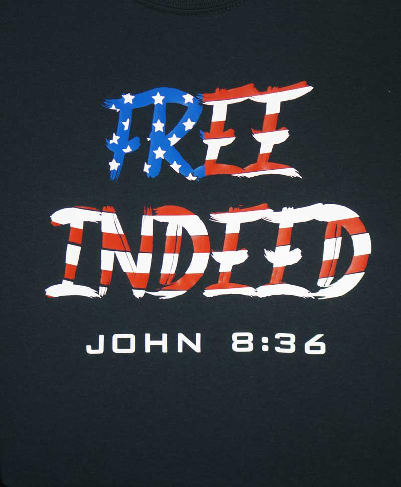 an example of a vinyl printed black shirt of 'Free Indeed' in the style of an American flag and the bible verse 'John 8:36'
