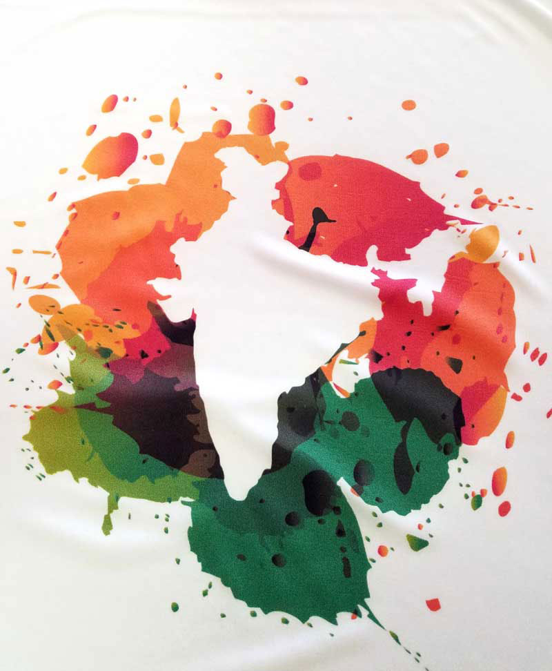 an example of a DTG-printed white shirt of the outline of the country of India in front of splashes of green and orange paint
