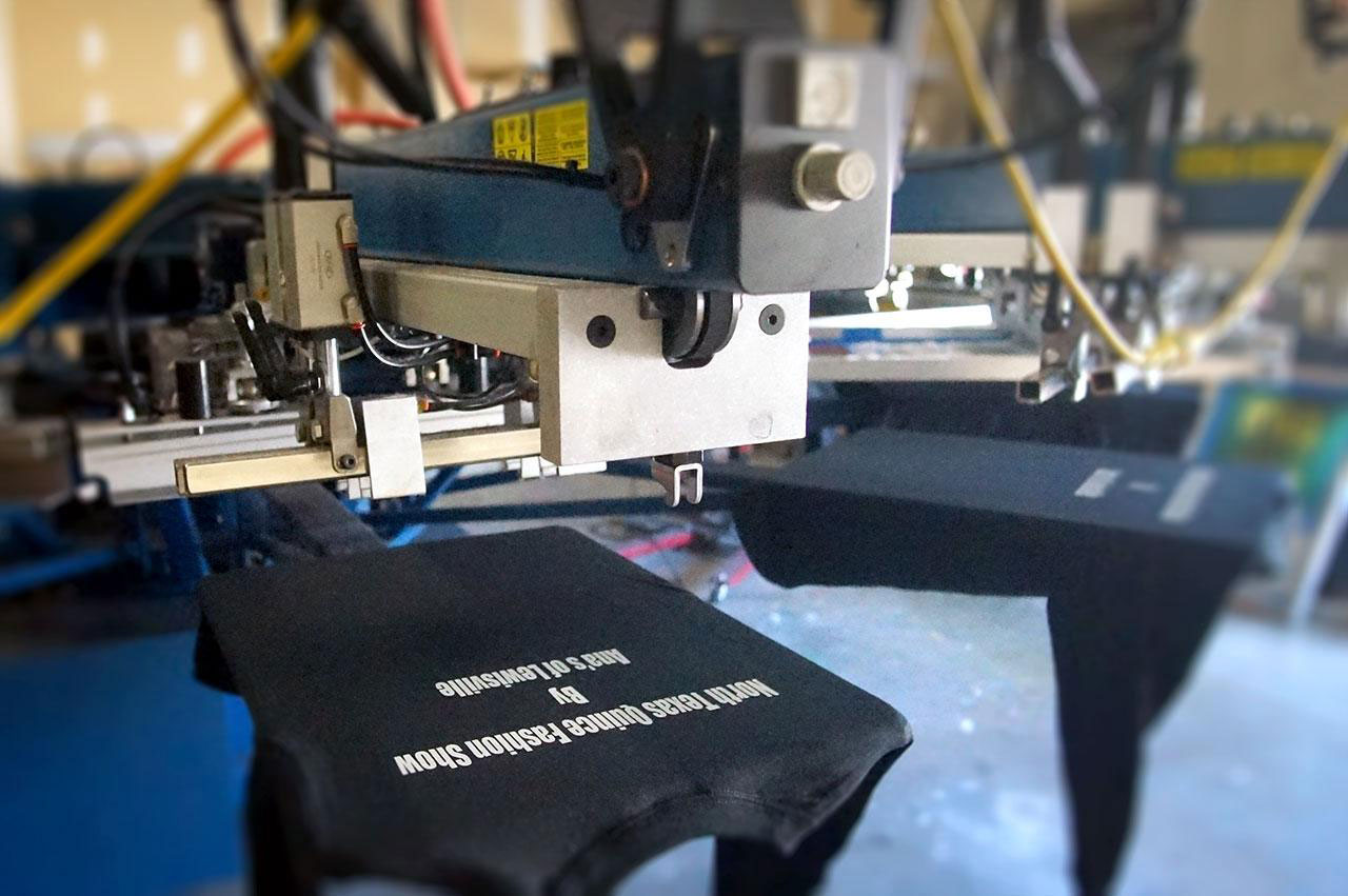 screen printing press machine with a black long sleeve shirt on the press